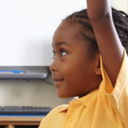 Black girl with her hand raised in classroom